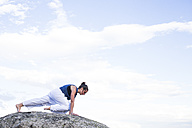Woman doing a yoga exercise on a rock - ABZF02131