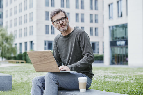 Mature man outdoors with laptop and takeaway coffee - RORF00866