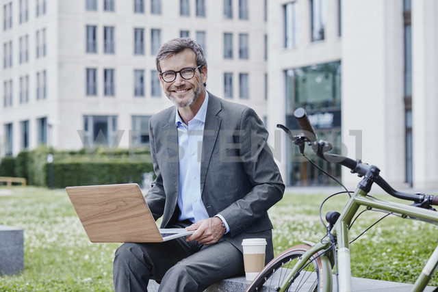 Portrait of smiling mature businessman outdoors with laptop, takeaway coffee and bicycle - RORF00872