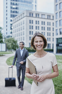 Portrait of smiling businesswoman outdoors with laptop and businessman in background - RORF00875