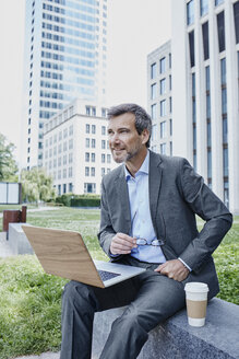 Smiling mature businessman outdoors with laptop and takeaway coffee - RORF00881