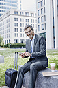 Smiling mature businessman outdoors with laptop, cell phone, takeaway coffee and rolling suitcase - RORF00893