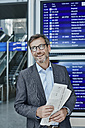 Smiling businessman with newspaper at timetable at the airport - RORF00899
