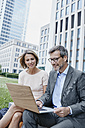 Smiling businesswoman and businessman sharing laptop outdoors - RORF00902