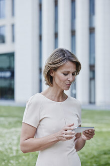 Businesswoman using cell phone outdoors - RORF00911