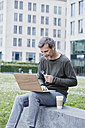 Mature man outdoors with laptop and takeaway coffee - RORF00932