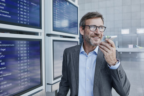 Smiling businessman with cell phone at timetable at the airport - RORF00938