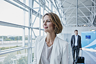 Confident businesswoman at the airport looking out of window - RORF00947