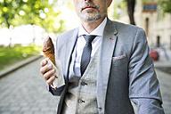 Mature businessman in the city eating ice cream - HAPF01705