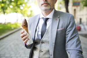 Mature businessman in the city eating ice cream - HAPF01705