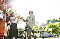 Businessman with bicycle buying take away coffee on the street - HAPF01708