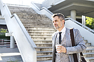 Confident mature businessman in the city with takeaway coffee - HAPF01717