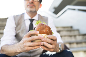 Businessman in the city sitting on stairs eating a hamburger - HAPF01720