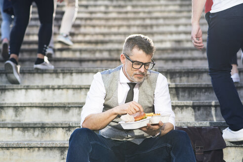 Businessman in the city sitting on stairs eating a hamburger - HAPF01723