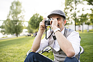 Mature businessman taking a picture with camera in park - HAPF01729