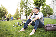 Confident mature businessman with bicycle and smartphone in the city park sitting on grass - HAPF01732
