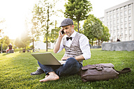 Confident mature businessman with laptop and smartphone in the city park sitting on grass - HAPF01735