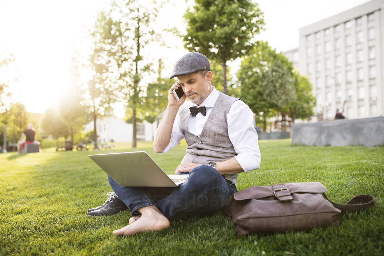 Confident mature businessman with laptop and smartphone in the city park sitting on grass - HAPF01735 - HalfPoint/Westend61