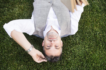 Mature businessman lying on grass - HAPF01741