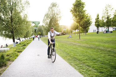 Confident mature businessman riding bicycle on waterfront promenade - HAPF01744