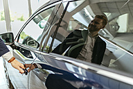 Customer looking at car in car dealership - ZEDF00663