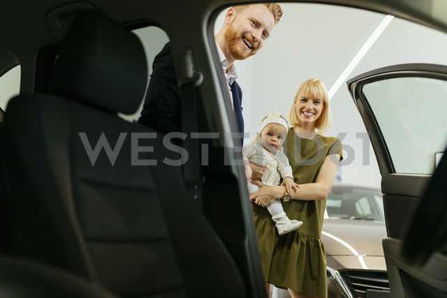 Family in car dealership choosing family vehicle - ZEDF00669