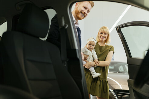 Family in car dealership choosing family vehicle - ZEDF00669