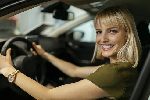 Blond woman choosing new car in car dealership - ZEDF00672