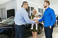 Family meeting seller of family vehicle in car dealership - ZEDF00678