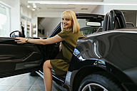 Blond woman choosing new car in car dealership - ZEDF00687