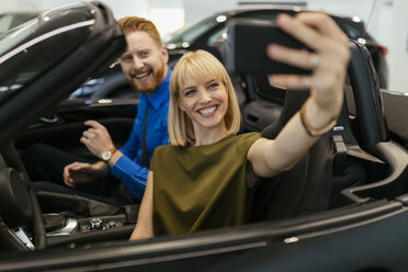Couple taking selfies, sitting in convertible in car dealership - ZEDF00690