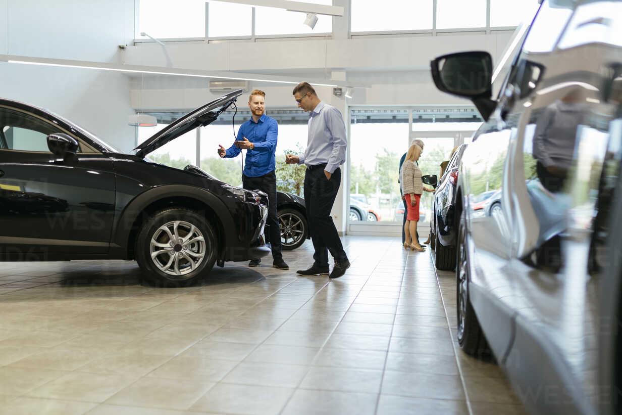 Salesman advising customer in car dealership - ZEDF00696 - Zeljko Dangubic/Westend61