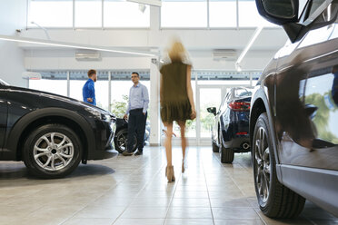 Car dealer talking to customer with woman walking in foreground - ZEDF00699