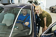 Couple looking for a new car in car dealership - ZEDF00702