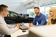 Salesperson advising couple in car dealership - ZEDF00705