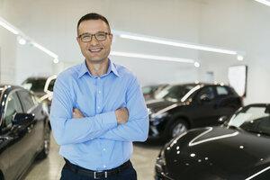 Car dealer standing in his shop - ZEDF00711