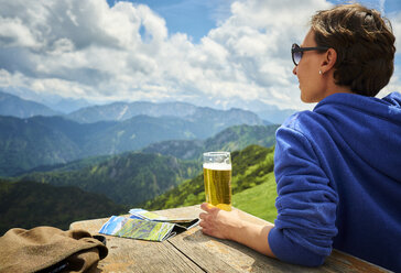Germany, Chiemgau, hiker on Hochfelln Mountain with glass of beer looking at view - DIKF00254
