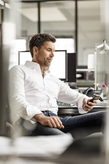 Businessman at desk in office using cell phone - PESF00696