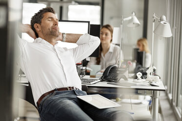 Businessman relaxing at desk in office - PESF00699