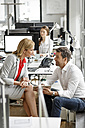 Businesswoman and businessman discussing at desk in office - PESF00711