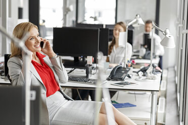 Businesswoman at desk in office on cell phone - PESF00714