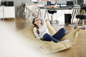 Young woman relaxing in bean bag in office - PESF00723