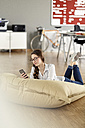 Young woman with cell phone lying in bean bag in office - PESF00726