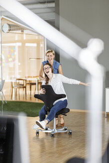 Playful employee pushing colleague on office chair - PESF00729