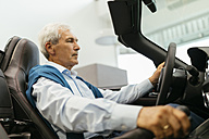 Senior man testing convertible in car dealership - ZEDF00718