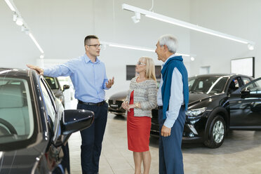 Senior couple couple talking with salesperson in car dealership - ZEDF00724