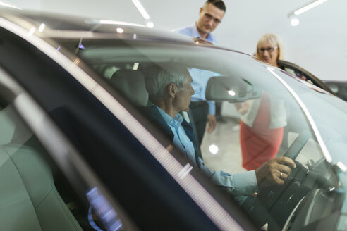 Senior couple couple talking with salesperson in car dealership - ZEDF00727