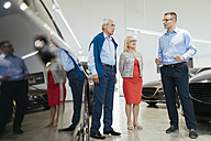 Senior couple couple talking with salesperson in car dealership - ZEDF00733