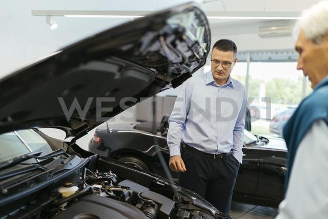 Salesman advising customer in car dealership - ZEDF00736