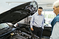 Salesman advising customer in car dealership - ZEDF00736